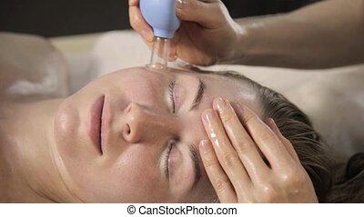 vacuum face massage, beautician does massage with vacuum...