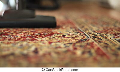 Vacuuming Colorful Carpet-Low Angle - A housewife uses a...