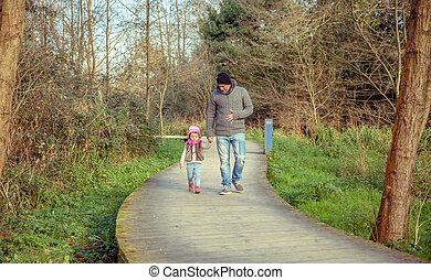 vader en dochter, samen lopend, holdingshanden