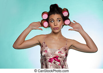 Vain pretty young woman showing her hair rollers