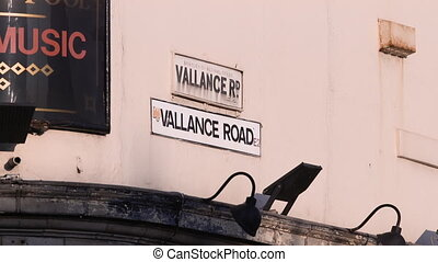 Closeup of a sign displaying Vallance road with bus driving past