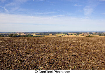 a plowed field with views of the vale of york under a blue sky in late summer