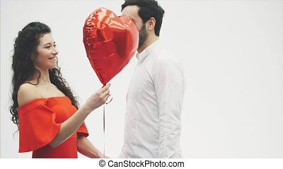 Valentine Couple. Beauty Girl and her Handsome Boyfriend holding heart shaped air balloon and kissing. Happy Joyful Family. Love. Happy Valentine's Day
