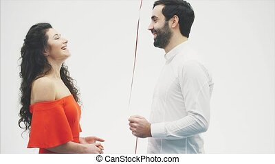 Valentine Couple. Beauty Girl and her Handsome Boyfriend holding heart shaped air balloon and kissing. Happy Joyful Family. Love. Valentine's Day.
