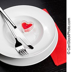 Valentine day dinner with table setting in red and elegant heart ornaments