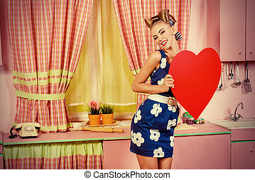 valentine day - Lovely pin-up girl stands on a pink kitchen...
