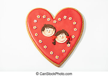 Valentine gift cookie. Red heart cookie with two children face inside. Love concept
