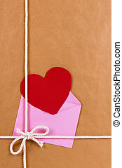 Valentine gift with red heart card or gift tag, brown paper package parcel background, copy space, vertical