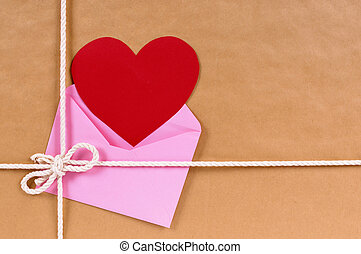 Valentine gift with red heart card or gift tag, brown paper package parcel background, copy space