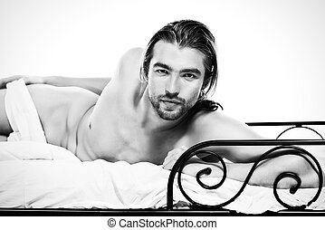 valentine - Handsome nude man lying in a bed. Isolated over...