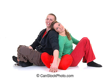 Two casual dressed young adults, teenage man and woman in love, holding hands abone heart pillow. studio shot.