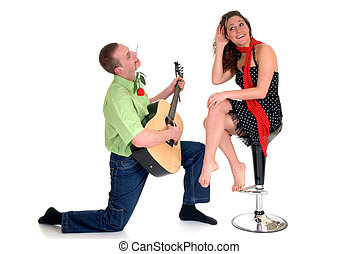Two casual dressed young adults, teenage man playing guitar and woman in love. studio shot.