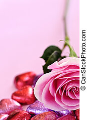 Pink rose with Valentine's chocolates wrapped in red and purple foil