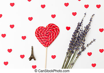 Valentine. Sweet lollipop in the shape of heart and a bouquet of lavender on a white background with hearts.