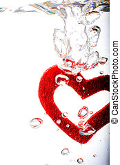 Valentine with red heart are steeped in water, macro