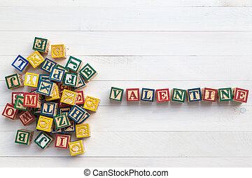 VALENTINE write in wooden alphabet block on white wooden board. Love concept or valentine day