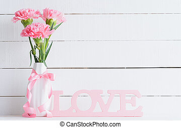 Valentines day and love concept. Pink carnation flower in vase with Wooden letters forming word LOVE written on white background.