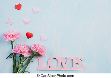 Valentines day and love concept. Pink carnation flower, Wooden letters forming word LOVE written with red heart on blue pastel background.