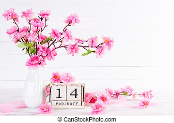 Valentines day and love concept. Pink Plum Peach Blossom in vase with February 14 text on wooden block calendar on white wooden background.