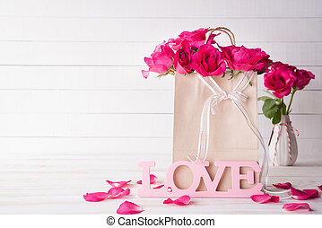 Valentines day and love concept. Pink roses in paper bag with Wooden letters forming word LOVE written on white wooden background.