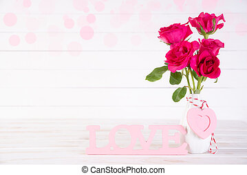 Valentines day and love concept. Pink roses in vase with wooden heart and with Wooden letters forming word LOVE written on white wooden background.