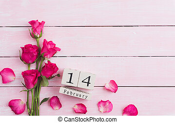 Valentines day and love concept. Pink roses with February 14 text on wooden block calendar on white wooden background.