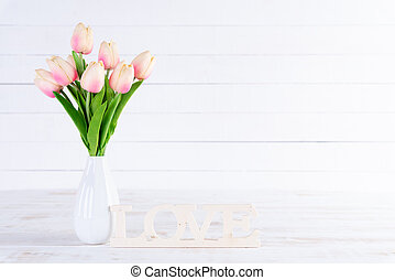 Valentines day and love concept. Pink tulips in vase with Wooden letters forming word LOVE written on white wooden background.