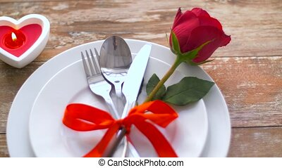 close up of red rose flower on set of dishes - valentines...