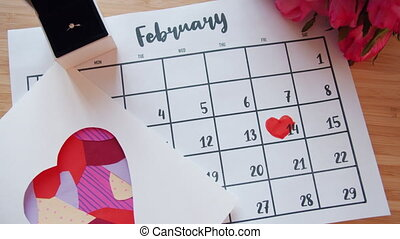 Valentine's day attributes on table - calendar with heart shape, flowers and ring