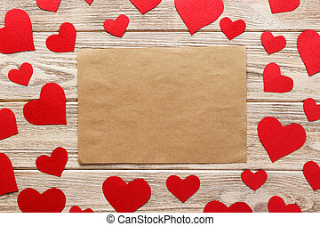 Valentines day background. Red hearts and empty letter on wooden background. Flat lay composition with copy space