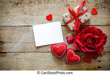 Red hearts, rose, message card and gift box on wooden table. Valentines Day background