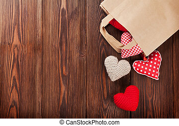 Valentines day hearts in shopping bag over wooden background. Top view with copy space