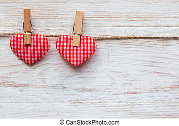 Valentine's day background with pair red hearts on clothespins at wooden border. Valentine's Day concept