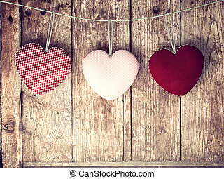 Valentines Day background with patterned textile hearts on old wooden