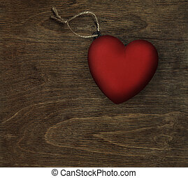 red heart on dark wood - valentine's day background with red...