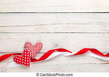 Valentines day background with toy hearts and ribbons