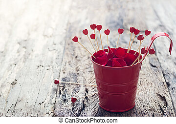 Valentines Day background with wood hearts in the red pot full of petal
