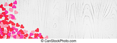Valentines Day banner with corner border of heart confetti over a white wood background with copy space
