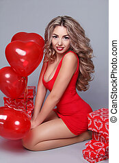 Valentine's Day. Beautiful happy woman with red heart balloons on gray background.