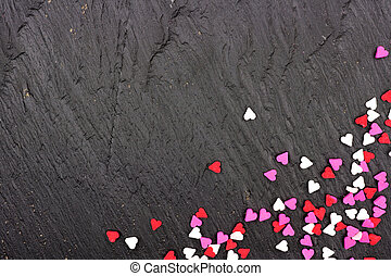 Valentines Day candy heart sprinkles corner border over a black background
