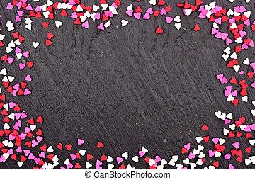 Valentines Day candy heart sprinkles frame over a black background