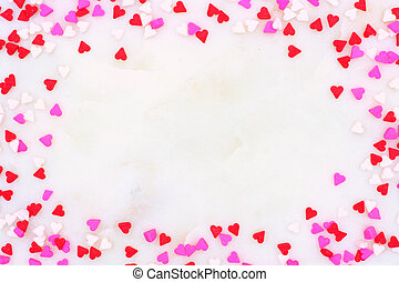 Valentines Day candy heart sprinkles frame over a white textured background