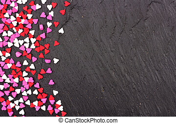 Valentines Day candy heart sprinkles side border over a black background