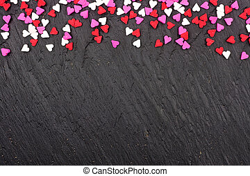 Valentines Day candy heart sprinkles top border over a black background