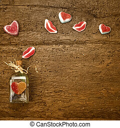 Valentines day card, bottle and gummy hearts on old wooden background with space for writing message or put photos