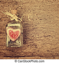 Valentines day card, bottle and gummy heart on vintage wooden background with space for writing message or put photos