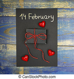 Valentine's Day Card with gift box, red hearts on wooden background