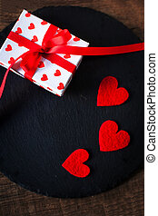 Valentine's Day card with red hearts, gift box with red ribbon and place for text