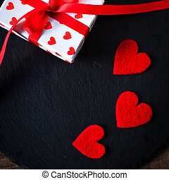 Valentine's Day card with red hearts, gift box with red ribbon and place for text. Valentines Day concept Background for design