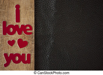 Valentine's Day card. Word Love with red hearts on wooden background. Greeting card concept. Top view